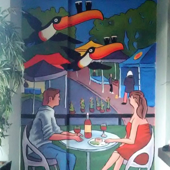 Mural of a couple eating at a restaurant with Guinness Pelicans flying overhead, Ireland