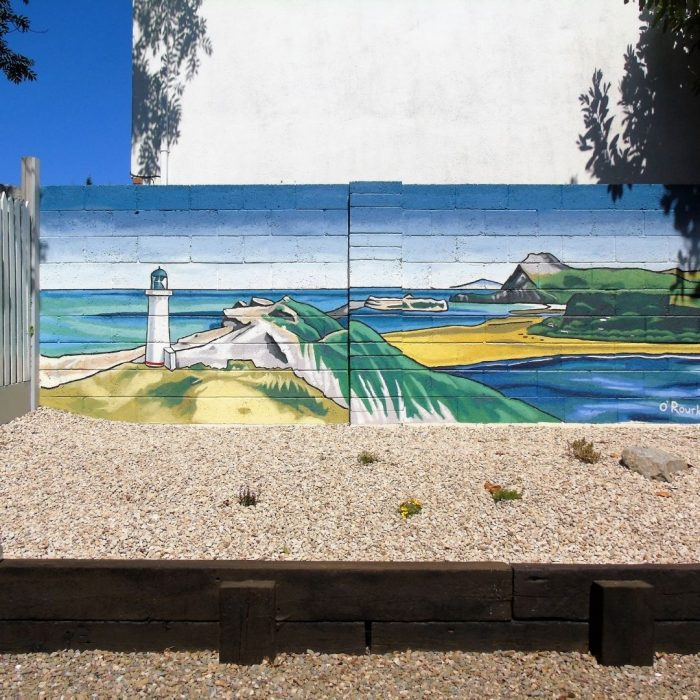 Mural of a beach scene and lighthouse in a back garden in Ireland by Artist David O'Rourke