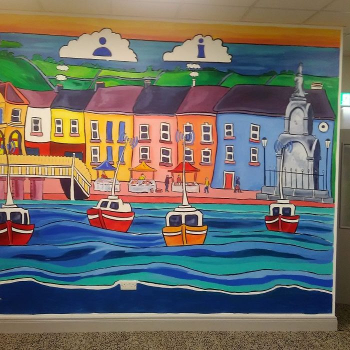 Mural of a colourful harbour town in Ireland by Irish Artist David O'Rourke