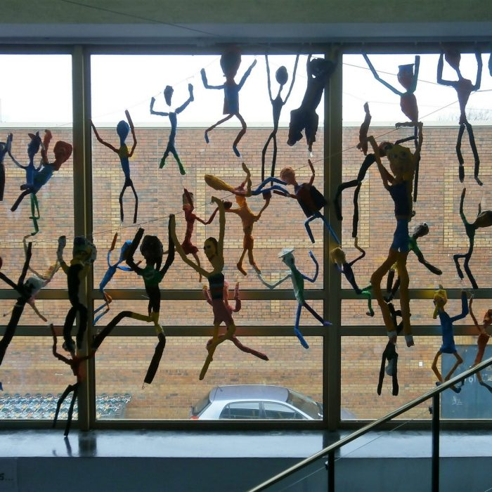 Colourful decorated wire figures displayed in a school on the window